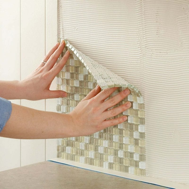 Fixing mosaic tile sheets to a wall.